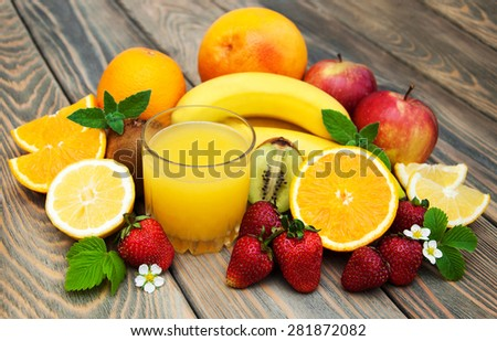 Glass with juice and fresh fruits on a old wooden background - stock photo