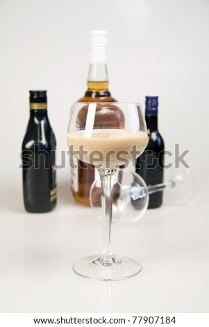 Glass with liquor and bottles with alcohol drinks on a background - stock photo