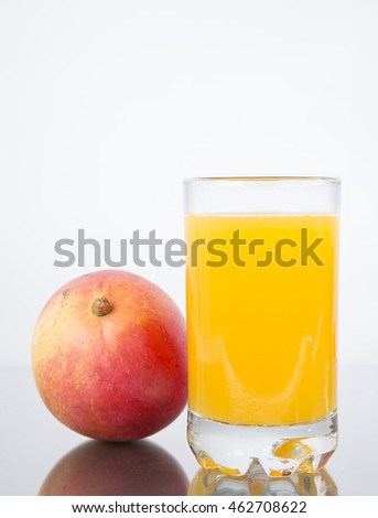Glass with mango juice and fruit.