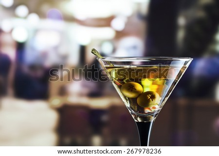 glass with martini , focus on a olives