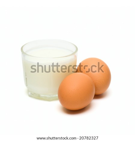 Glass with milk and eggs isolated on white - stock photo