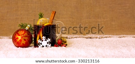 Glass with mulled wine on a snow  background .Christmas mulled wine and red ball. - stock photo