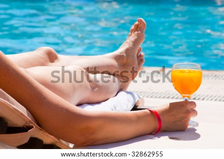 Glass with orange juice on the brink of pool