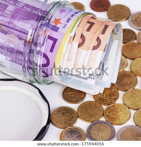 Glass with paper money and coins