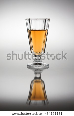 Glass with plum wine in back light. - stock photo