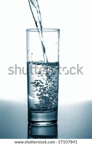 glass with pouring water with reflection on white