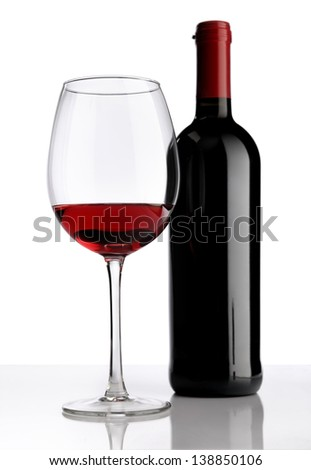 glass with red wine bottle on white background - stock photo