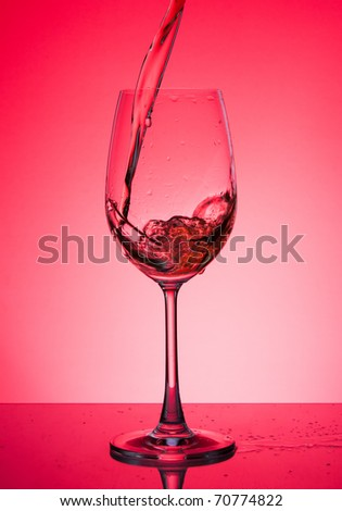 Glass with rose wine on a red background - stock photo