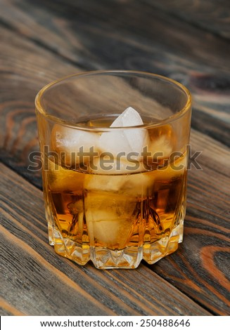 Glass with Scotch and ice on old wooden background