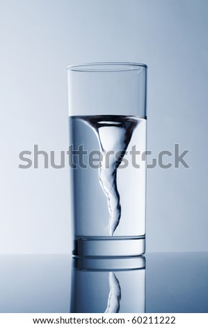 glass with spring water against a blue background - stock photo