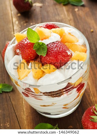 Glass with strawberry-peach parfait and whipped cream. Shallow dof.  - stock photo