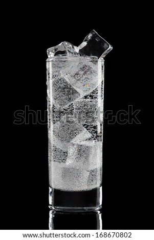 Glass with water and ice. Isolated on black. - stock photo