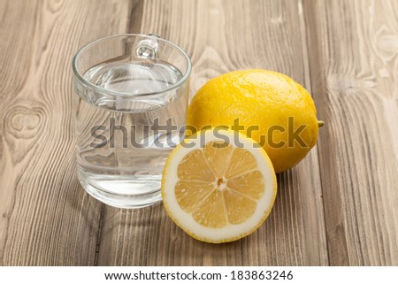 Glass with water and lemon on wooden table - stock photo