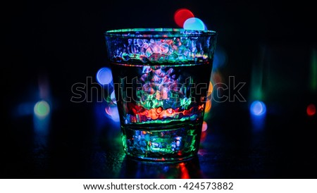 Glass with water on colorful bokeh background. Glass with light bokeh in background. Glass and blurred abstract lights. Beautiful abstract wallpaper of glass in front of color bokeh background.