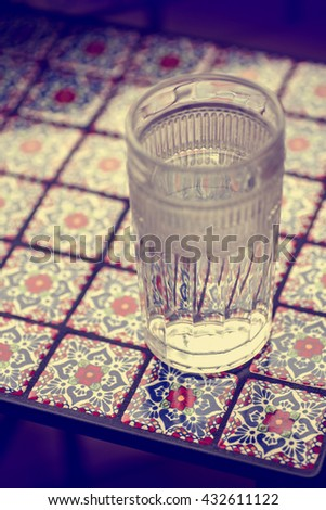 Glass With Water On The Table With Mexican Talavera Tile In Red, Purple,  White