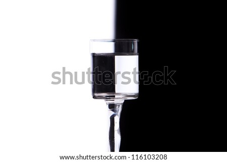 glass with water on white and black background