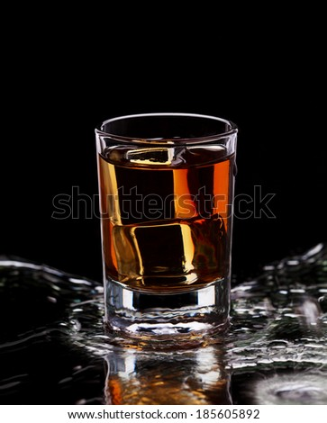 Glass with whiskey and ice cubes on dark background with water splash, selective focus - stock photo