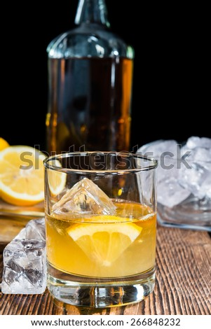 Glass with Whiskey Sour and ice cubes (close-up shot) - stock photo