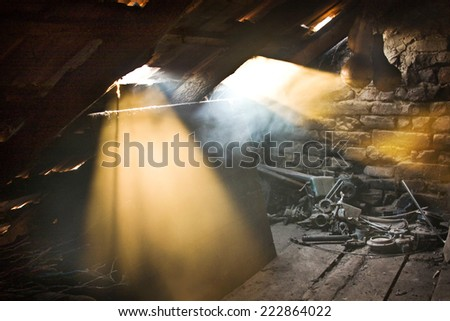 Glass, wooden and metallic objects in the attic with dust and spiderwebs in a beautiful, moody light  - stock photo
