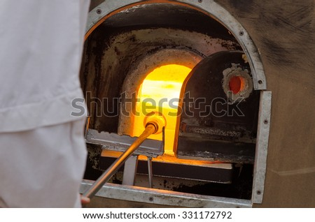 glassblower at work in the factory - stock photo