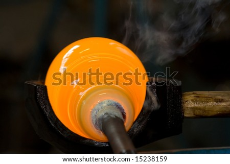 Glassblowing - Shaping a glass bubble - stock photo