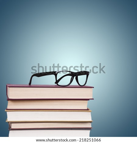 glasses above the stacked books, business and objects - stock photo