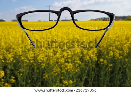 Glasses against cloudy landscape background - stock photo