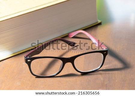 Glasses and a big book - stock photo