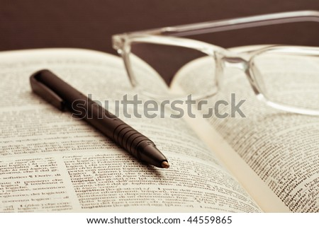 Glasses and a pen on a book