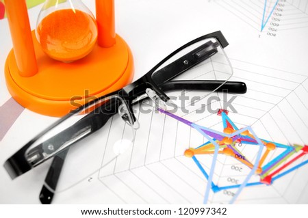 Glasses and a sand-glass on graphs. - stock photo