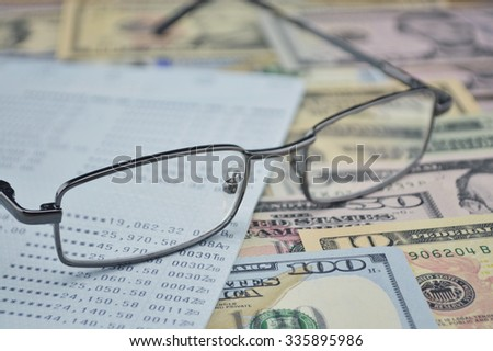 Glasses and account book on dollar bank note money