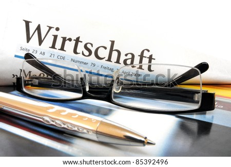 """Glasses and ball pen on top of a multicolored cover with lettering """"Economy"""" in German language - stock photo"""