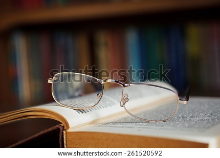 glasses and book in the library - stock photo