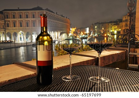 Glasses and bottle of a red wine in Venice. - stock photo