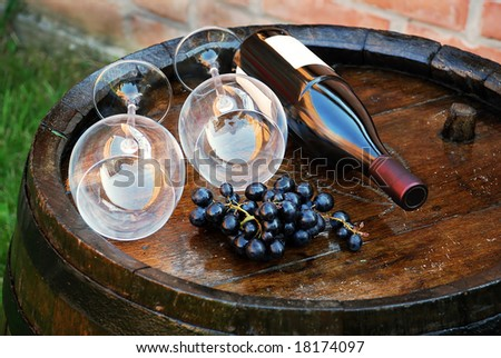 glasses and bottle over wine barrel - stock photo
