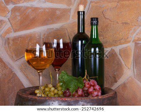 Glasses and bottles of wine, cheese and grapes on old barrel with iron rings - stock photo