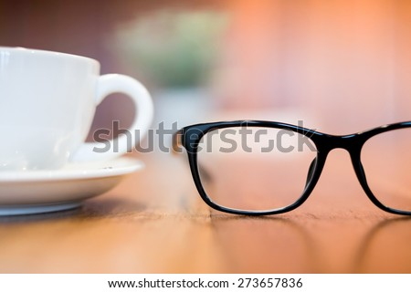 glasses and cup of coffee on wood desk