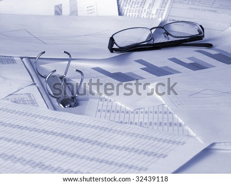 Glasses and financial documents. Toned blue. Shallow DOF.
