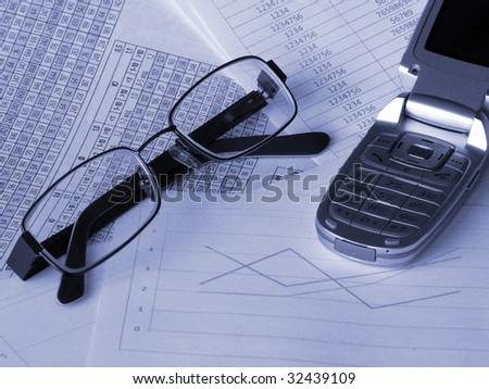 Glasses and mobile phone on financial documents. Toned blue. Shallow DOF. - stock photo