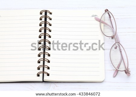 Glasses and note book on the white wooden table - stock photo