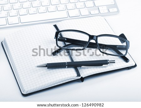 Glasses and office supplies. Blue toned closeup - stock photo