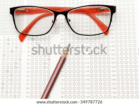 glasses and pencil on Standardized test form with answers bubbled in and a pencil, focus on answer sheet