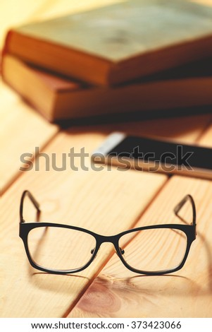 glasses, books and mobile phone on a wooden table