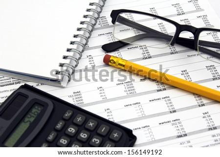glasses, calculator, pencil and paper bills - stock photo