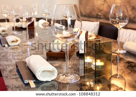Glasses, candle on table in sushi restaurant, focus on glass - stock photo