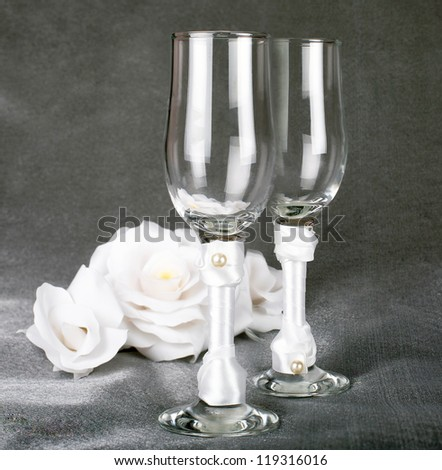 glasses for champagne wedding with the decoration of white satin and pearls are on the grey dark surface on a black background with white roses in the background - stock photo