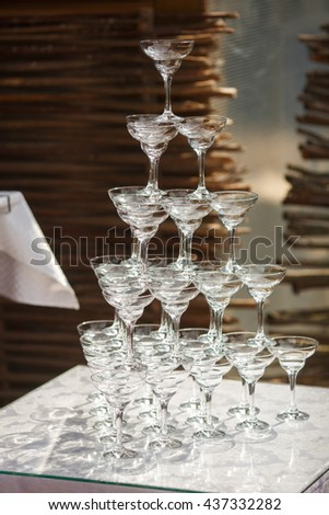 Glasses for cocktails stand in a for of pyramid - stock photo