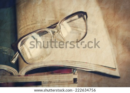 glasses for reading on a stack of magazines. With the effect of crumpled paper - stock photo