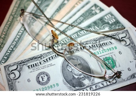 glasses for vision correction and a small pile of dollars