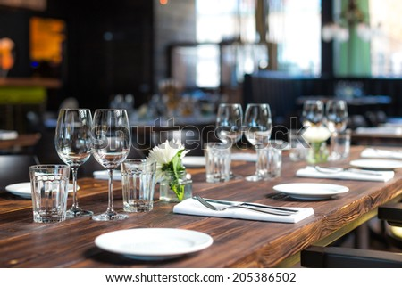 Glasses, forks, knives, plates on a table in restaurant served for dinner - stock photo